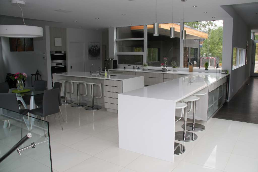 Custom built kitchen with l-shaped counters, large windows and stool seating. White and grey interior design.